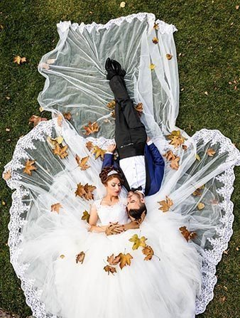 Bride and Groom ground laying on beautiful white circular train