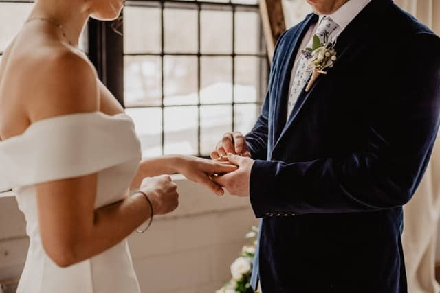 Closeup of groom putting wedding ring onto brides finger