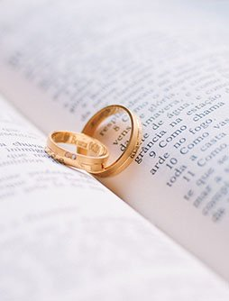 Golden Wedding Rings laying on open fold of a bible