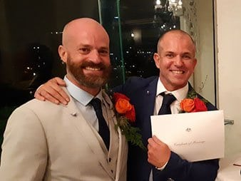 Male grooms same sex marriage holding marriage certificate