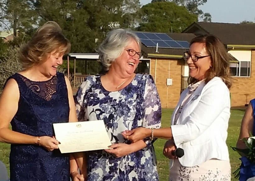 Older same sex married ladies receiving marriage certificate from celebrant